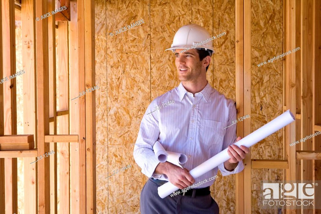 Stock Photo: Architect with blueprints in hardhat in partially built house.