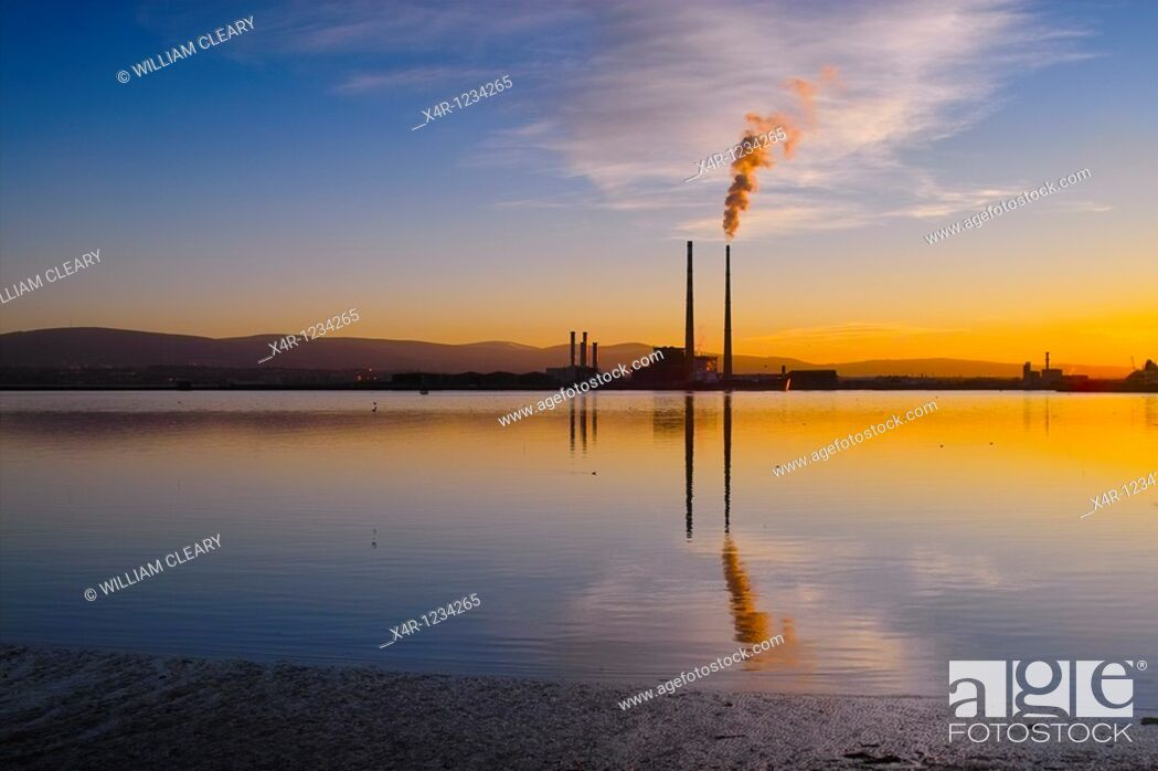 Stock Photo: Sunset over Dublin Bay, Ireland. To the right is the iconic Poolbeg Power Station, with smoke billowing from its right cooling tower.