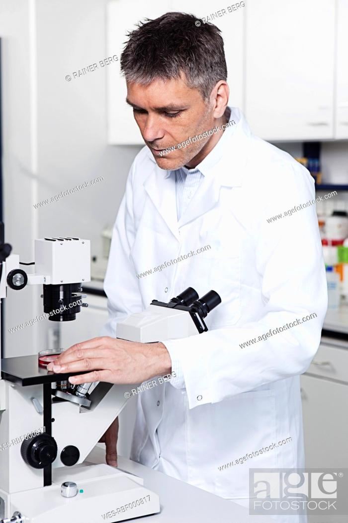 Stock Photo: Germany, Bavaria, Munich, Scientist with microscope in laboratory.