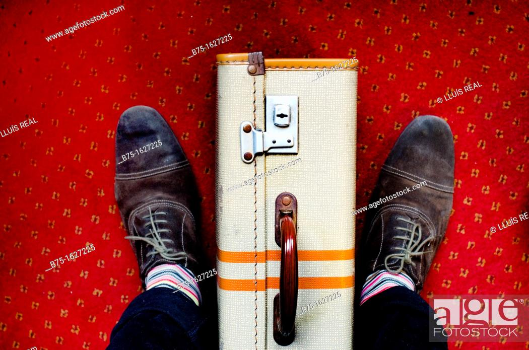 Stock Photo: old suitcase at the foot of a man waiting.