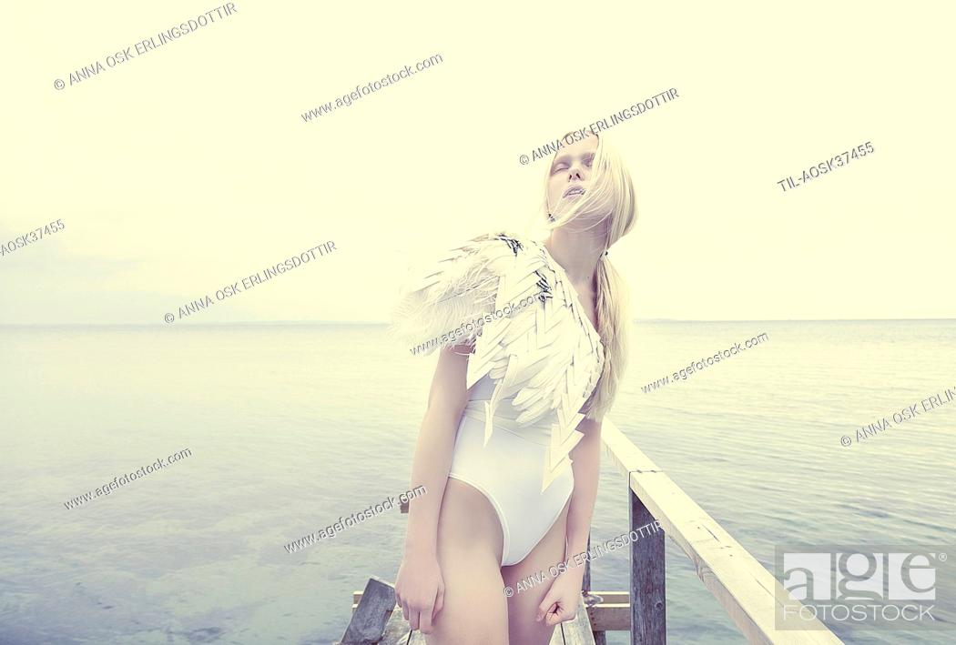 Stock Photo: Female teenager with blonde hair standing by sea.