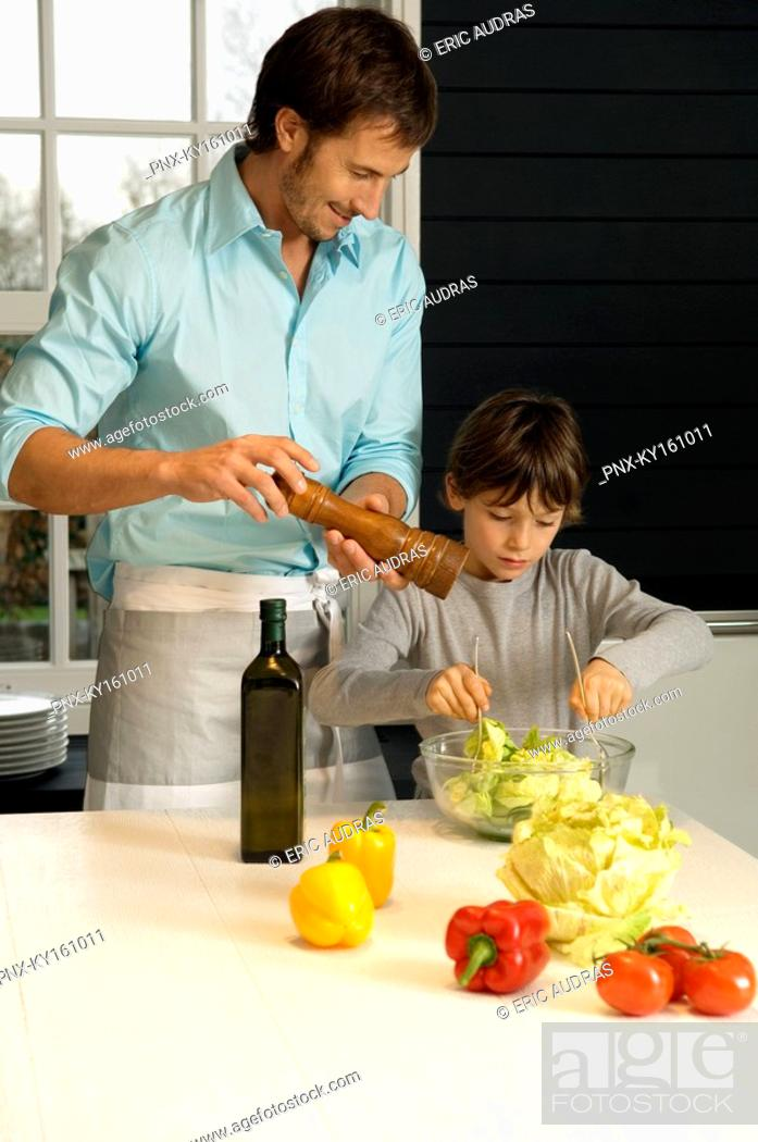 Stock Photo: Mid adult man preparing food with his son in the kitchen.