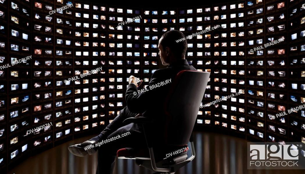 Stock Photo: Man watching video on monitors.