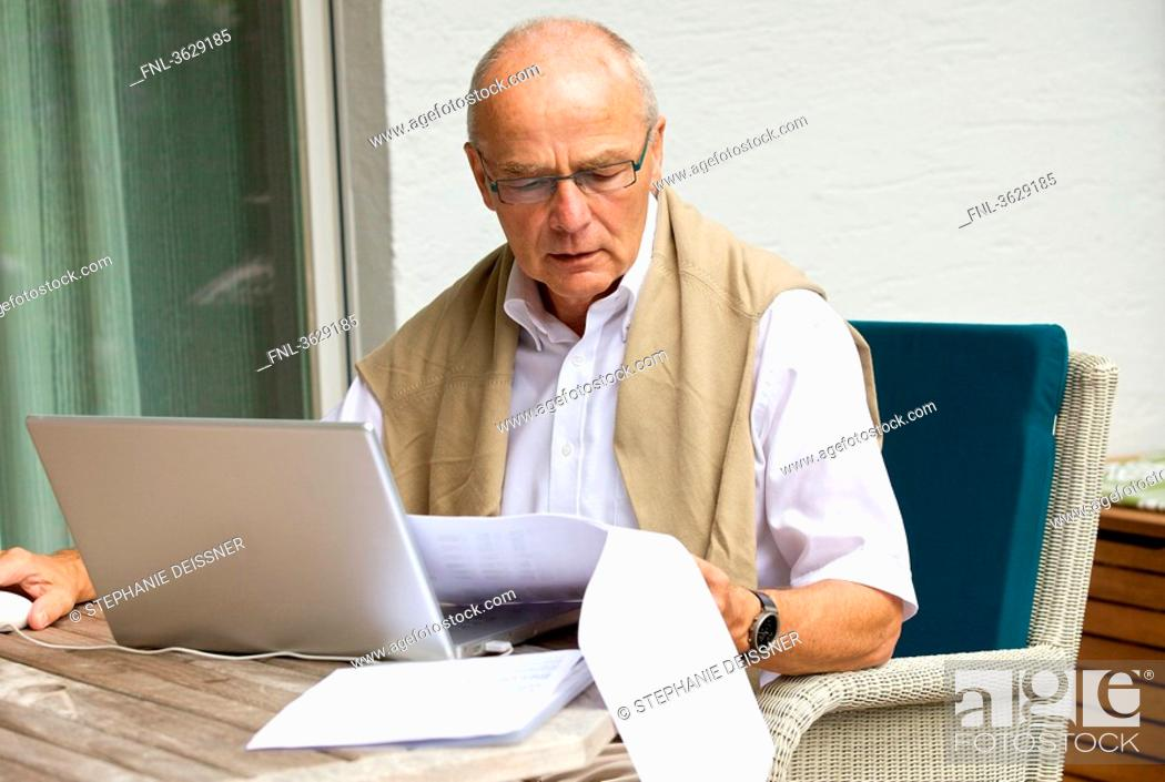 Stock Photo: Senior man using laptop on terrace.