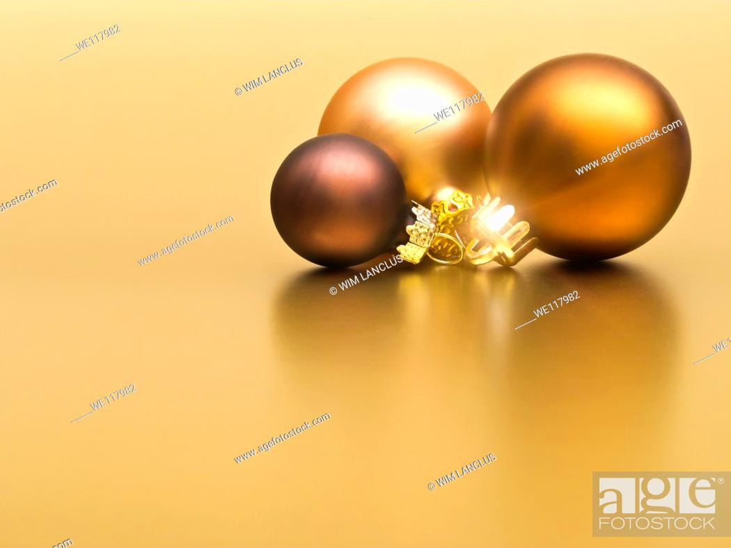 Stock Photo: Christmas baubles on golden background.