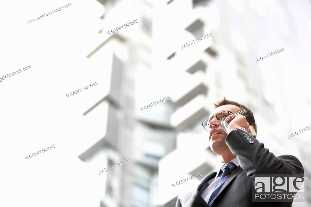 Stock Photo: Businessman using mobile phone in front of tall building low angle view.