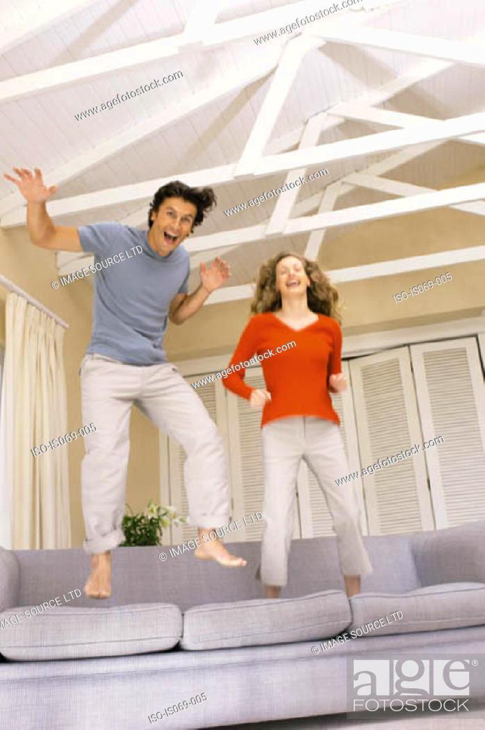 Stock Photo: Couple jumping on sofa.