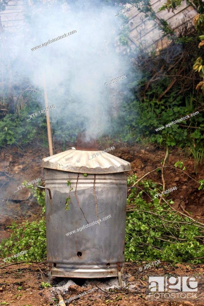 Stock Photo: home garden incinerator burning green tree and bush waste during gardening work in the uk.