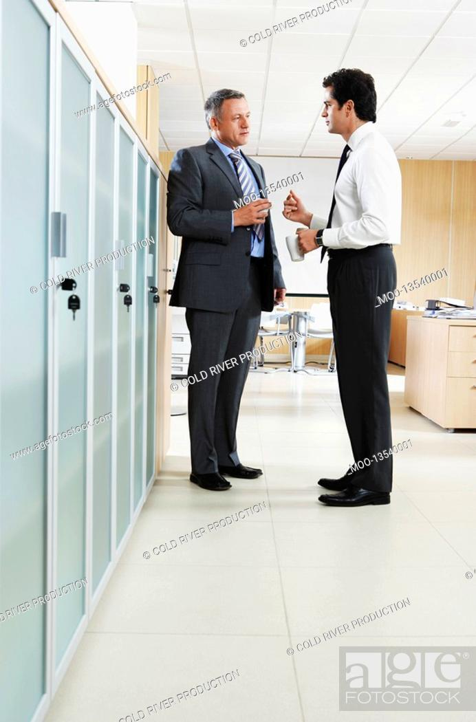 Stock Photo: Two businessmen talking in office corridor.