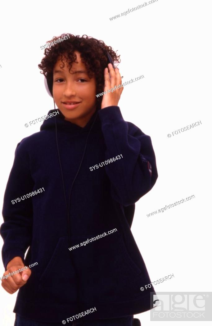 Stock Photo: Young boy listening to music on large earphones.