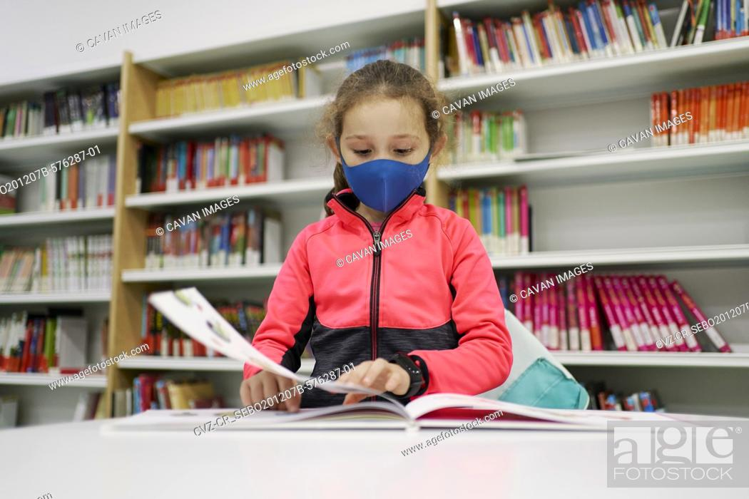 Stock Photo: Little girl wearing a medical mask and reading a book in a libra.