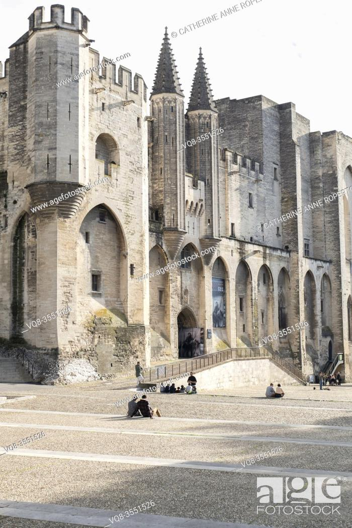 Imagen: Imposing pinnacled towers and fortifications of the papal palace above groups of seated school children below, Avignon; Provence; France.