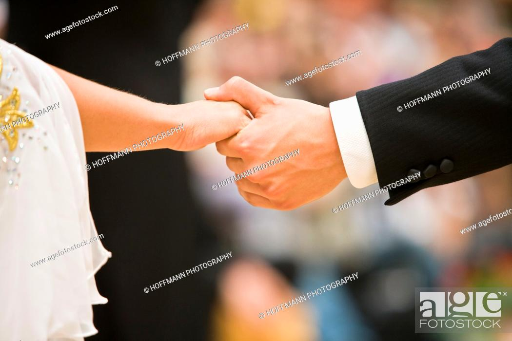 Stock Photo: Couple holding hands at a dancing competition, Germany, Europe.