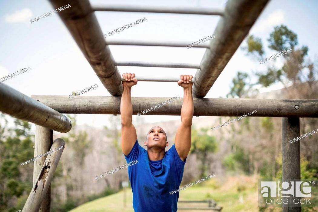 Stock Photo: Fit man climbing monkey bars during obstacle course.