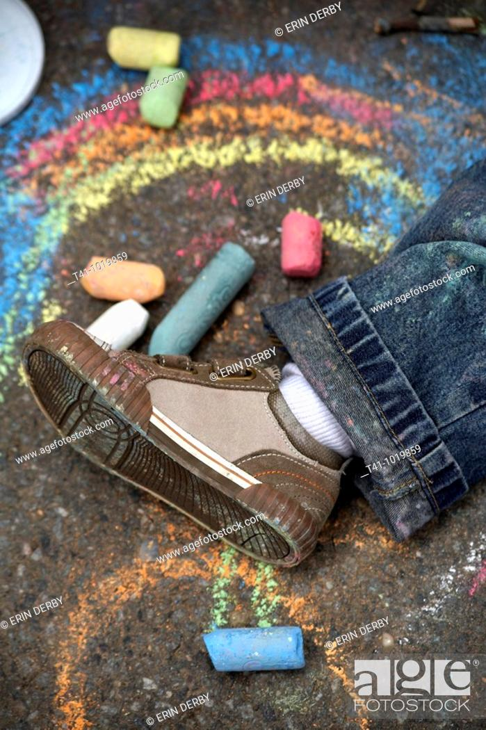 Stock Photo: An overhead photograph of a 2 year old boy's shoe on a sidewalk surrounded by chalk and drawings.