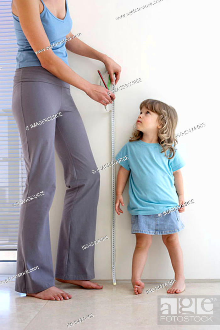 Stock Photo: Mother measuring daughters height.