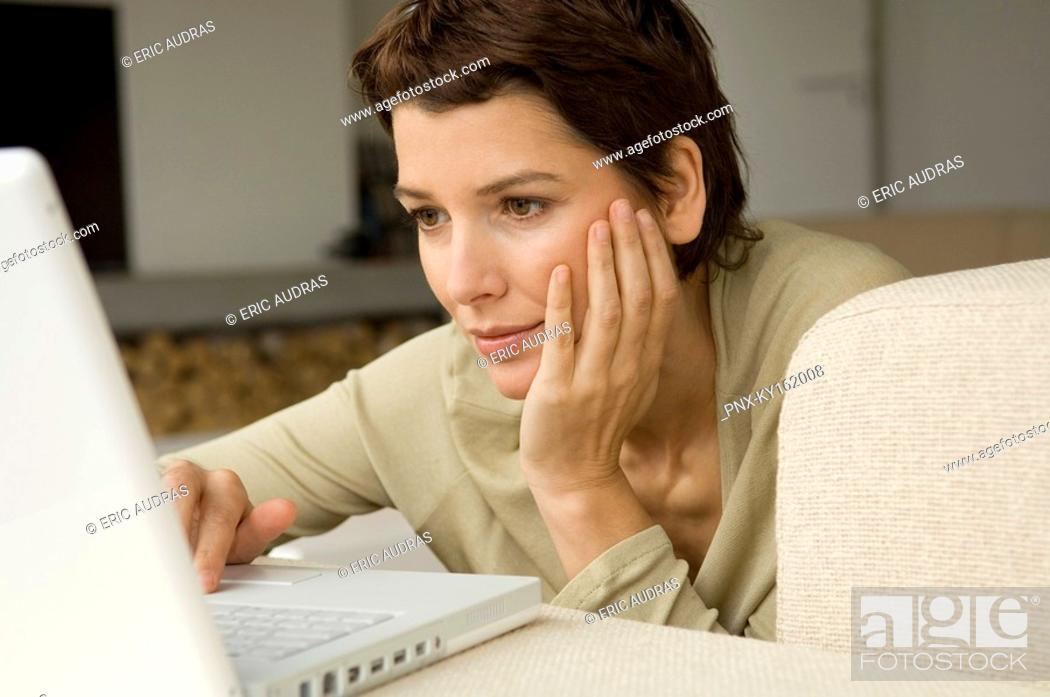 Stock Photo: Mid adult woman working on a laptop in a living room.