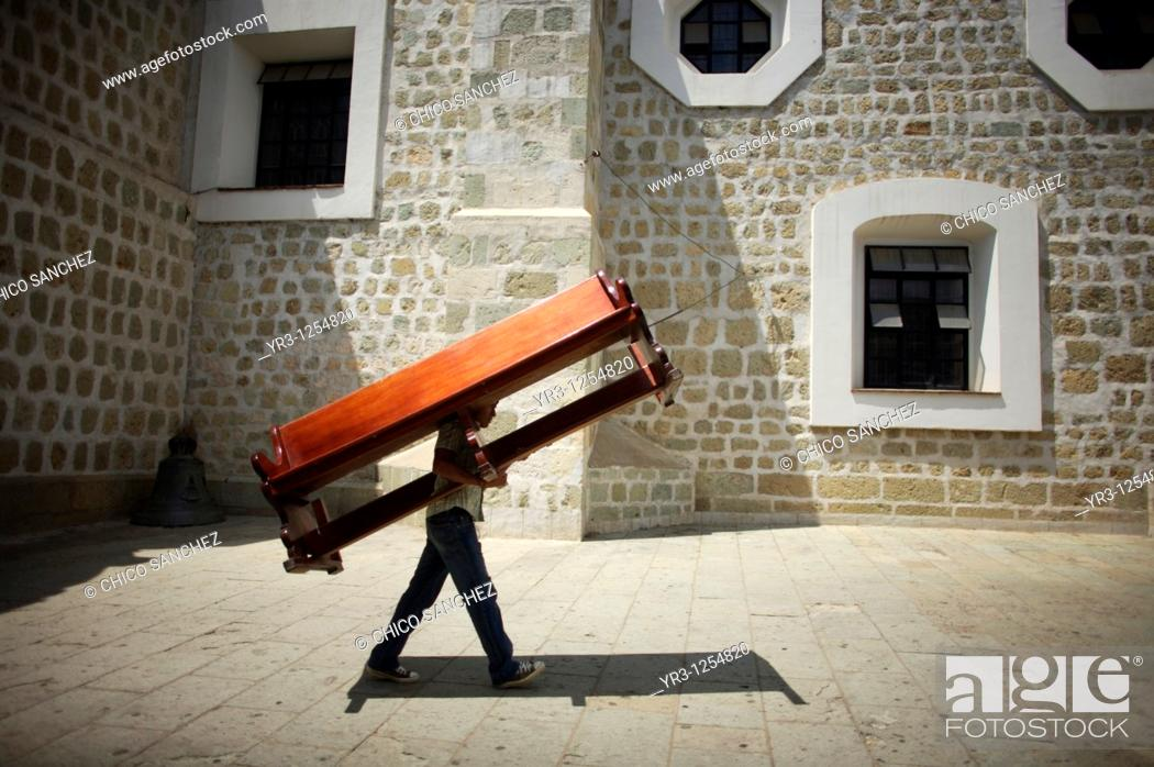 Stock Photo: A man carries a church bench to the Basilica de la Soledad, or Solitude Basilica, after a holy week procession in Oaxaca, Mexico.