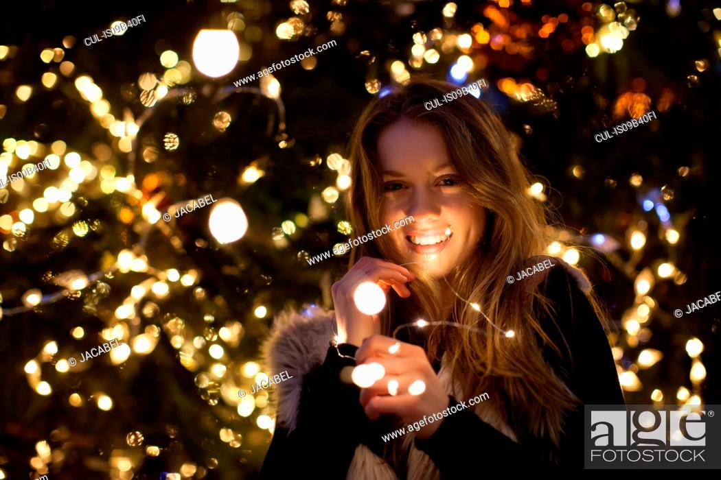 Stock Photo: Young woman with lights in her hand, tree in background.
