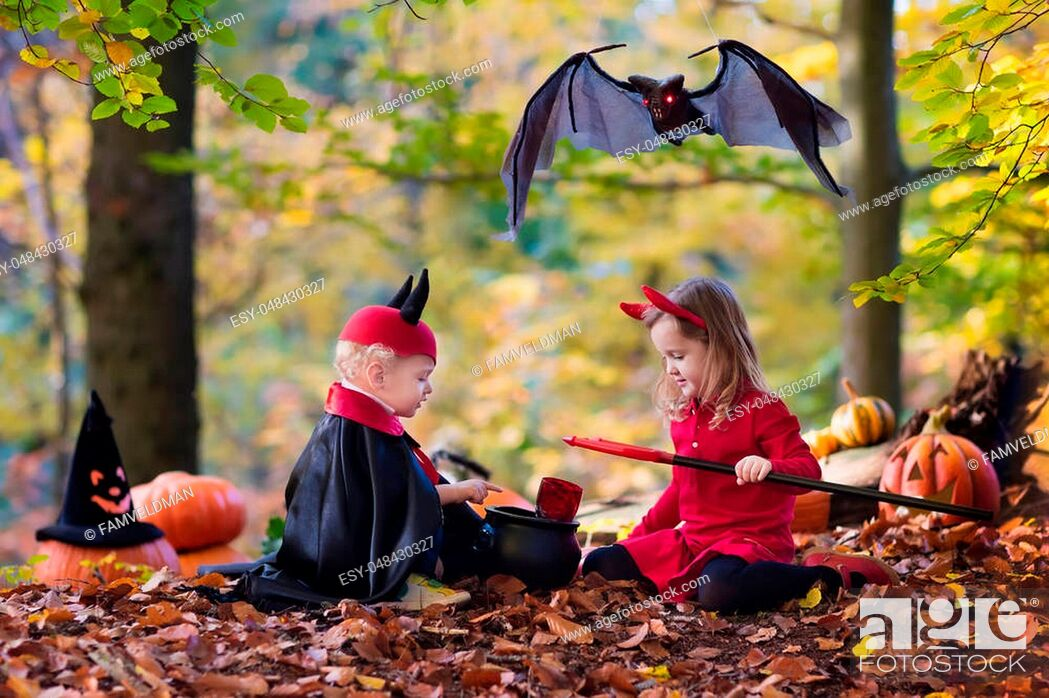 Stock Photo: Two funny kids wearing devil and vampire costume with red horns and trident trick or treating on Halloween. Children dressed up as witch play in autumn park.