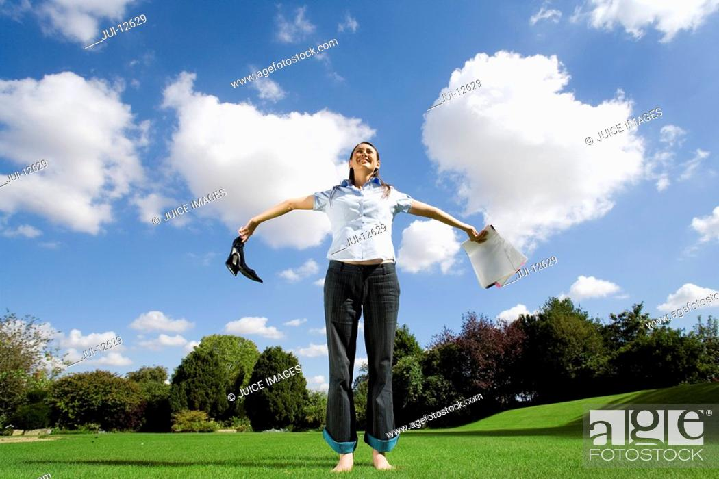Stock Photo: Woman on grass holding out paperwork and shoes, low angle view.
