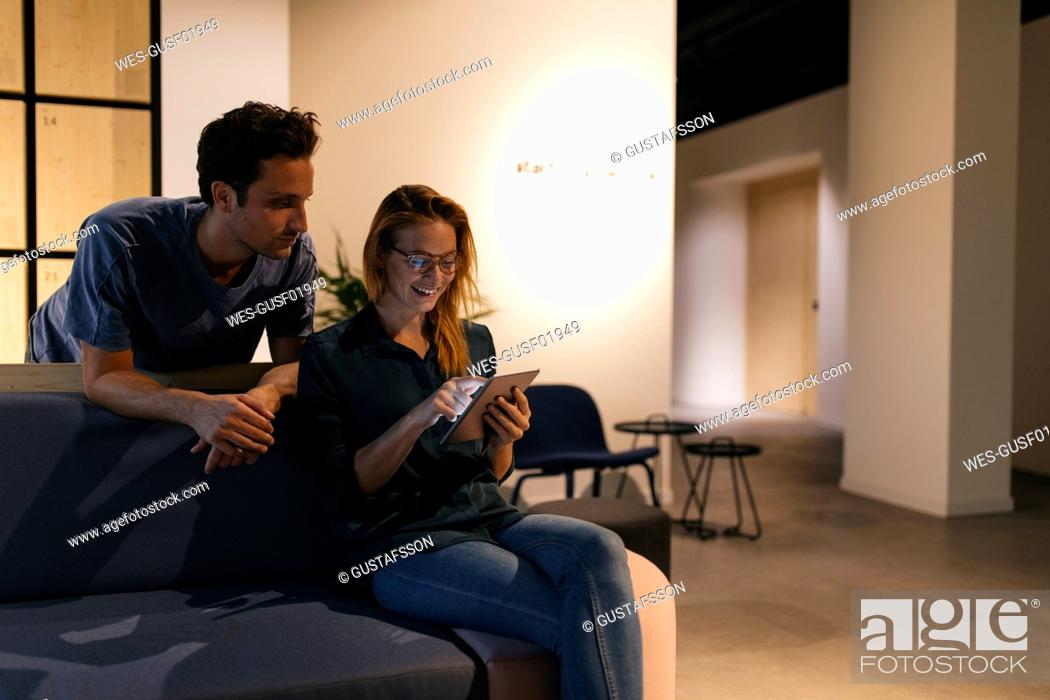 Stock Photo: Young man and woman using tablet on couch.