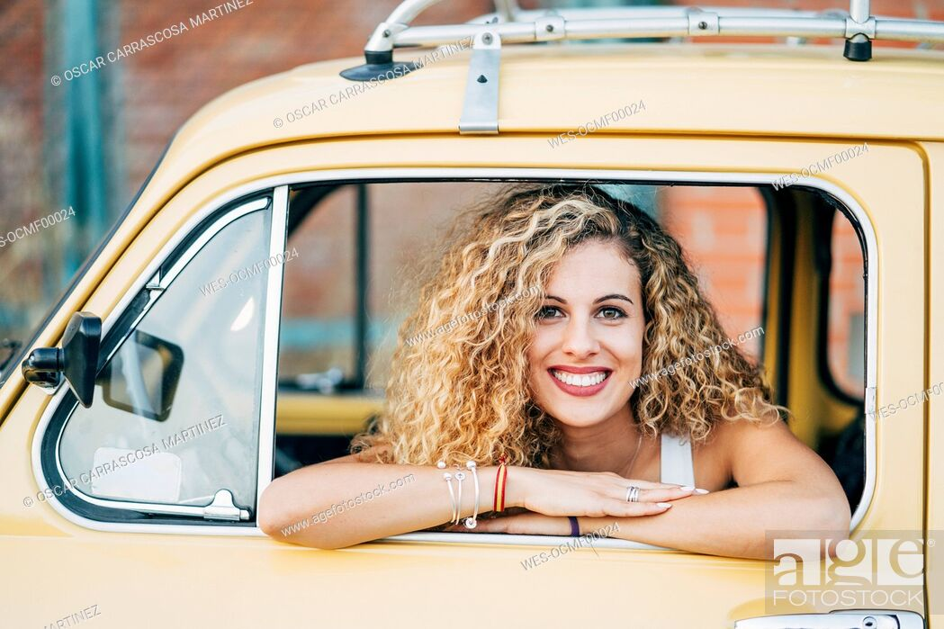 Stock Photo: Portrait of happy blond woman looking out of window of classic car.