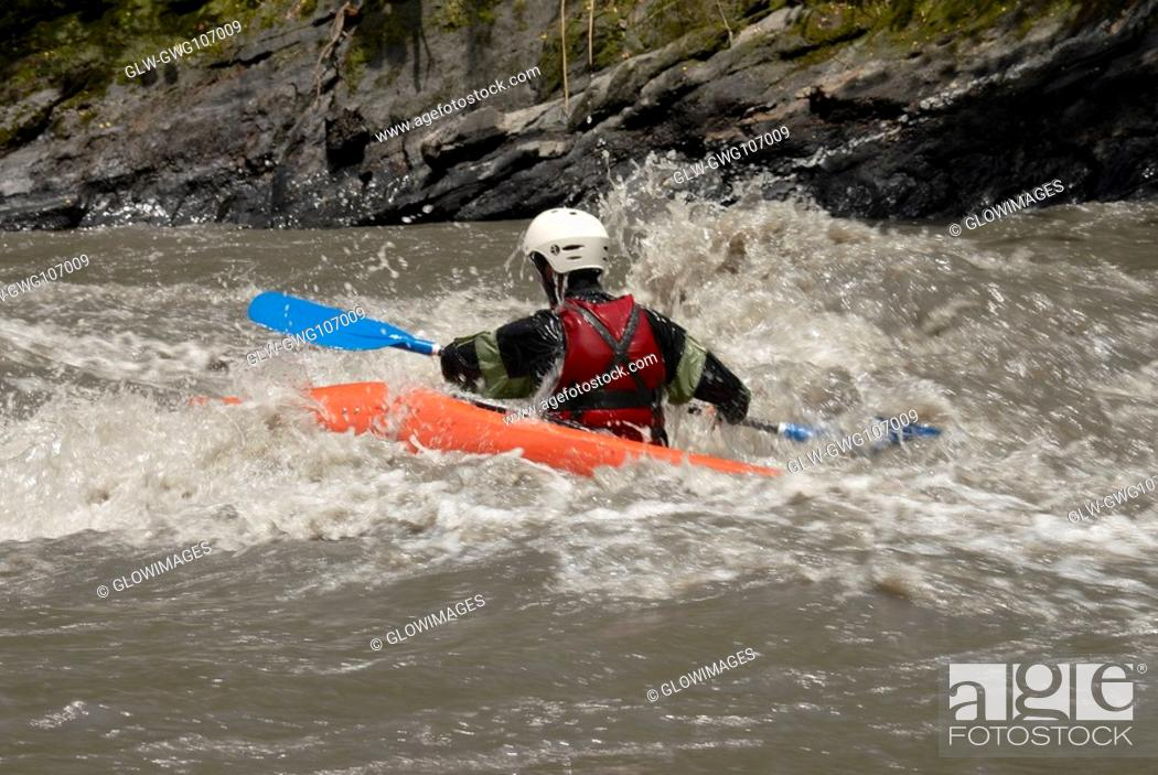 Stock Photo: Rear view of a person kayaking in a river.