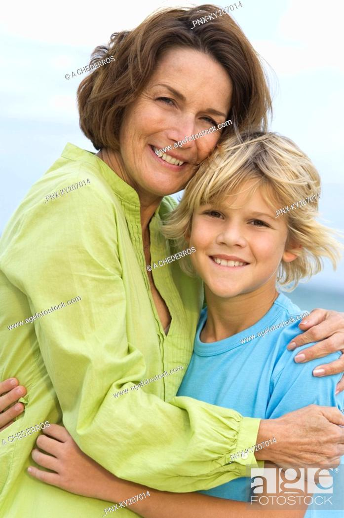 Stock Photo: Woman smiling with her grandson on the beach.