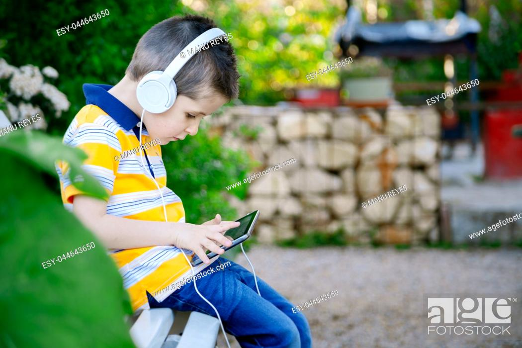 Stock Photo: boy listening to music with withe headphones on the outside. Madrid, Spain.