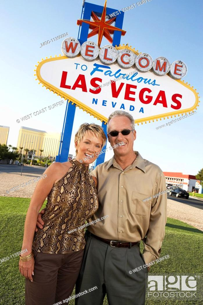 Stock Photo: Couple in front of Welcome to Las Vegas sign portrait.
