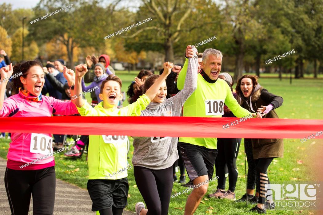 Stock Photo: Enthusiastic family running, nearing charity run finish line.
