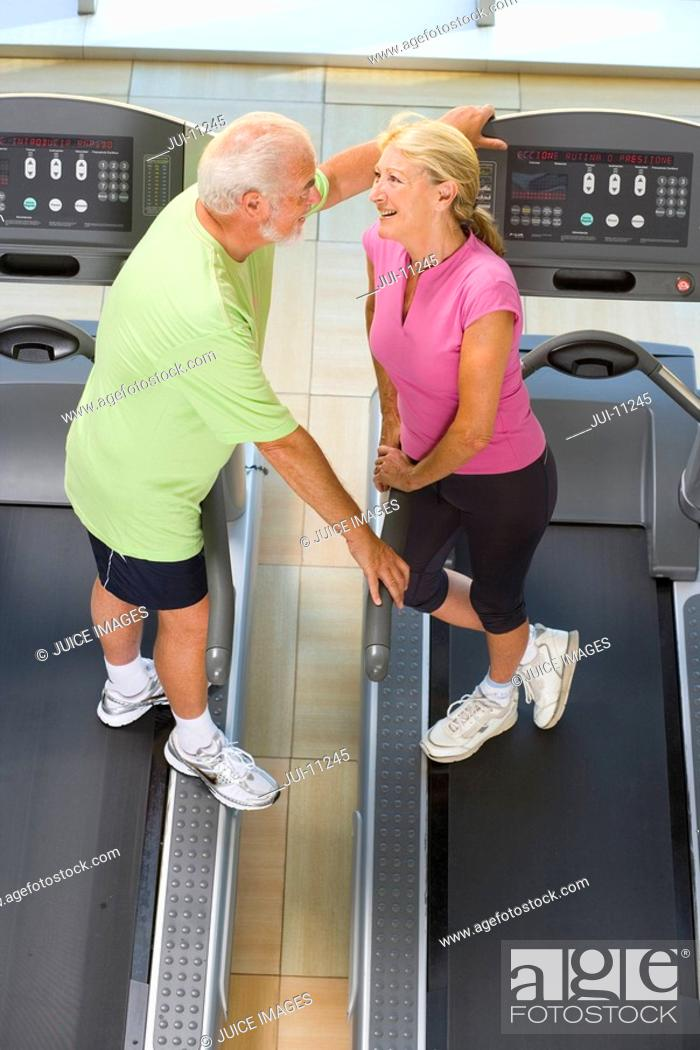 Stock Photo: Senior man and woman on treadmills, in conversation, elevated view.