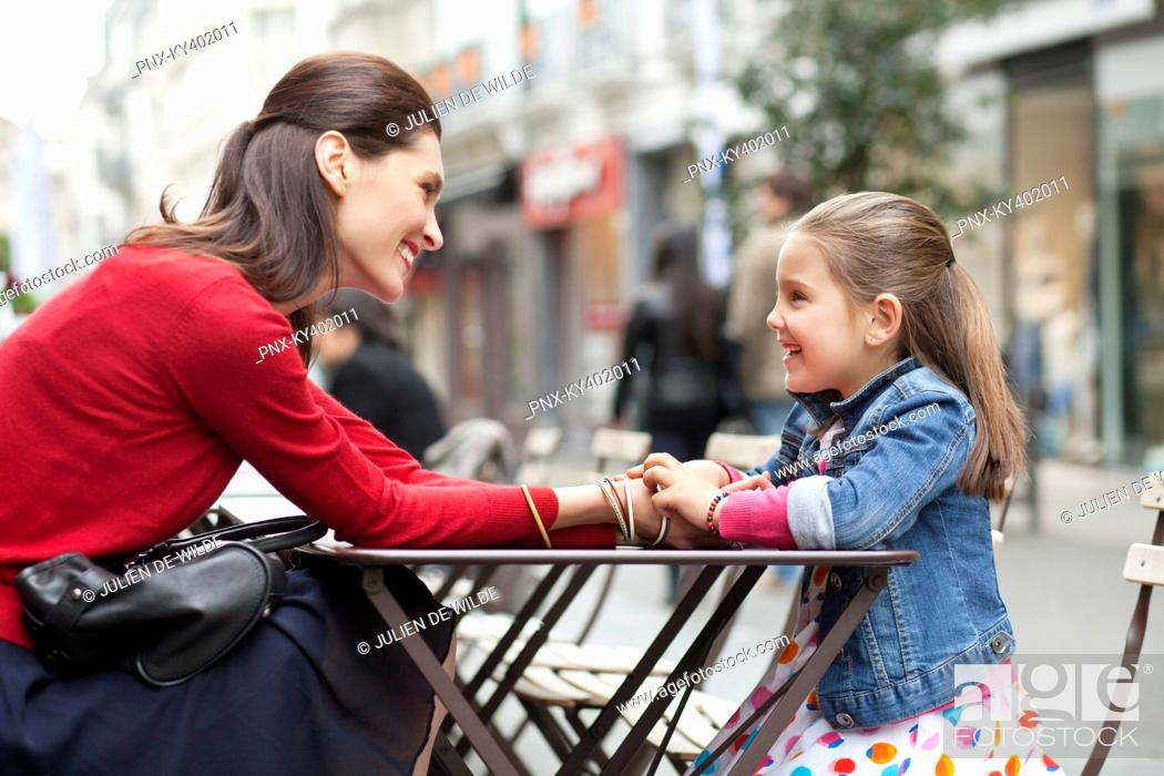 Stock Photo: Woman and her daughter sitting at sidewalk cafe.
