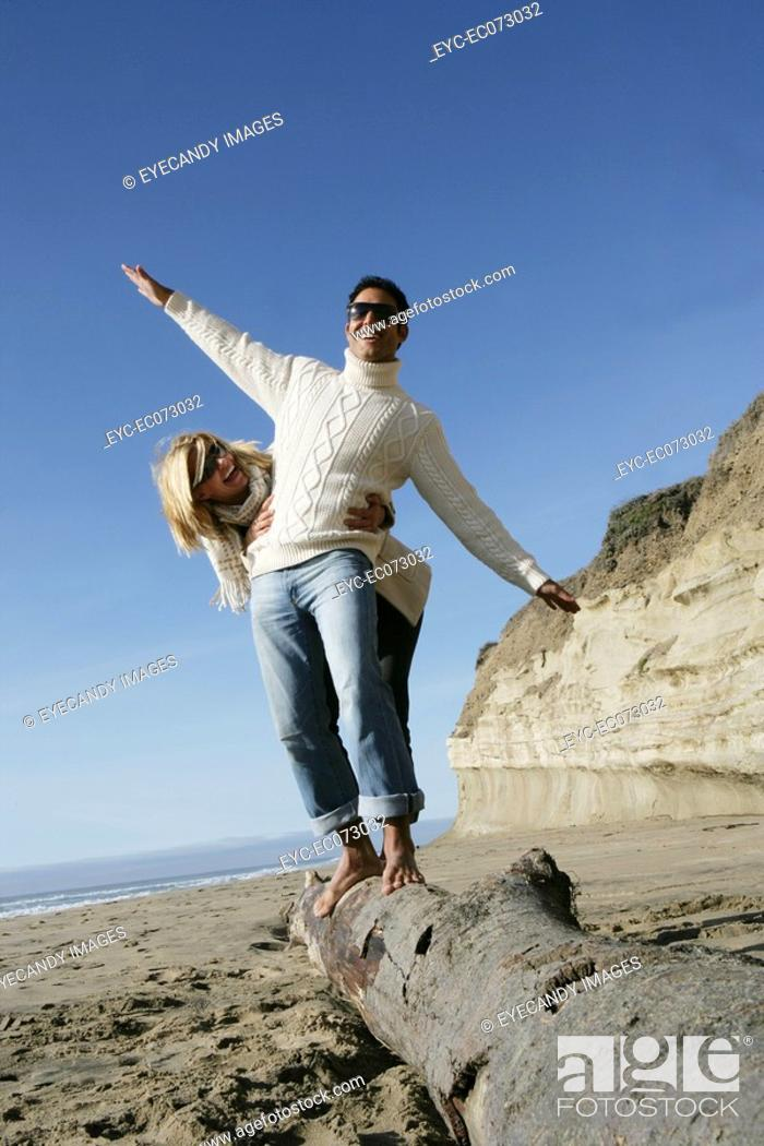 Stock Photo: Young couple balancing on log at beach.