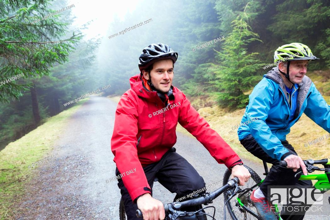 Stock Photo: Father and son mountain biking in woods.
