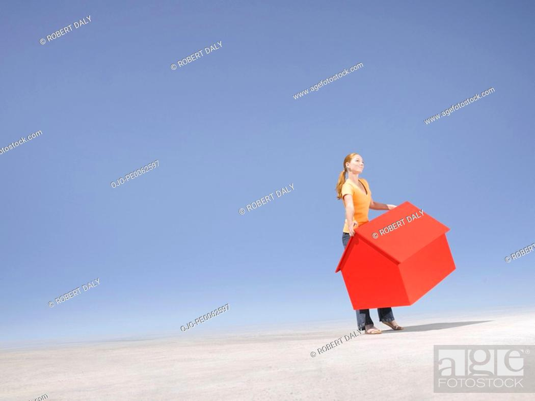 Stock Photo: Woman holding small model house in desert.