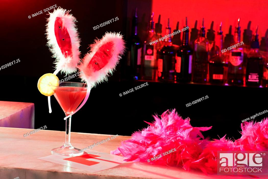 Stock Photo: Pink cocktail, bunny ears and L plate on bar.