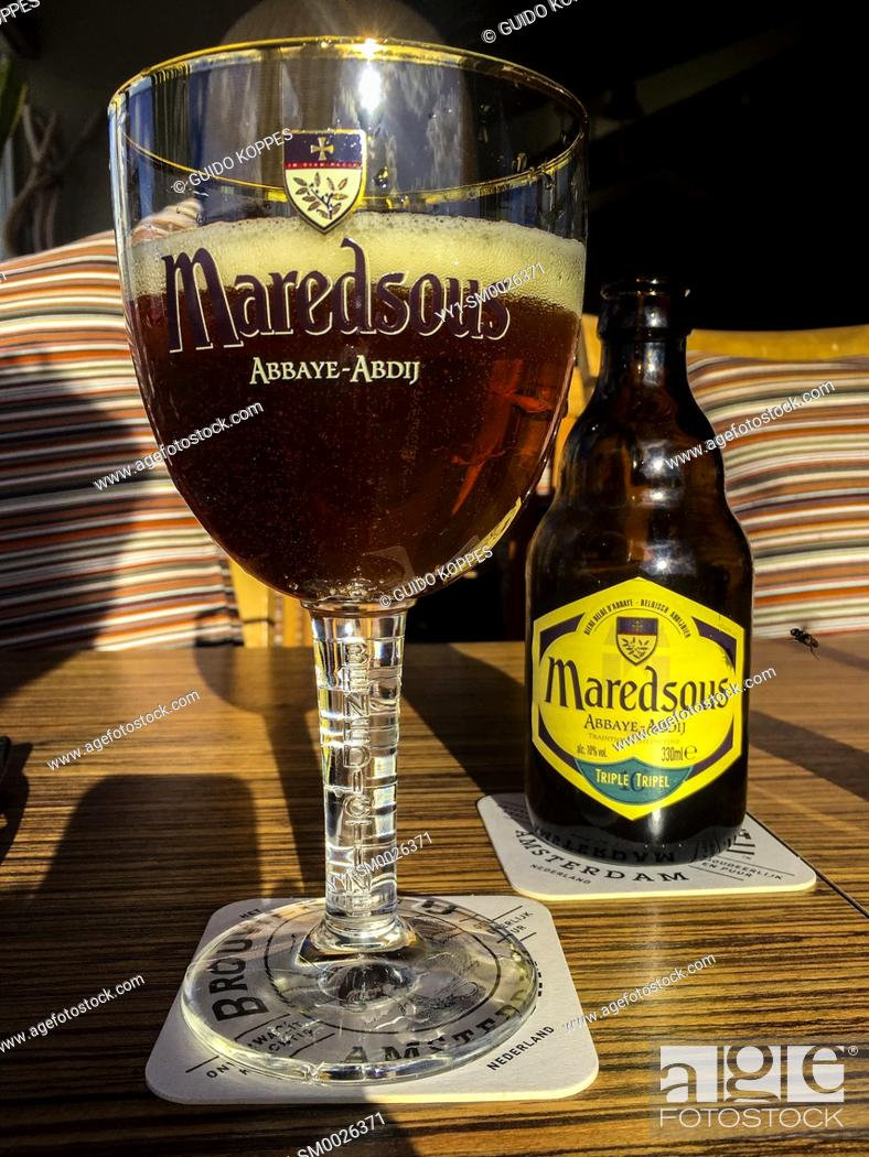Imagen: Hoek van Holland, Netherlands. Glass and bottle of craftbeer on a sunny table inside a beach house.