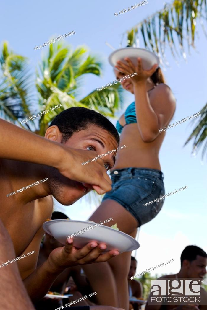 Imagen: Young man eating at beach party.