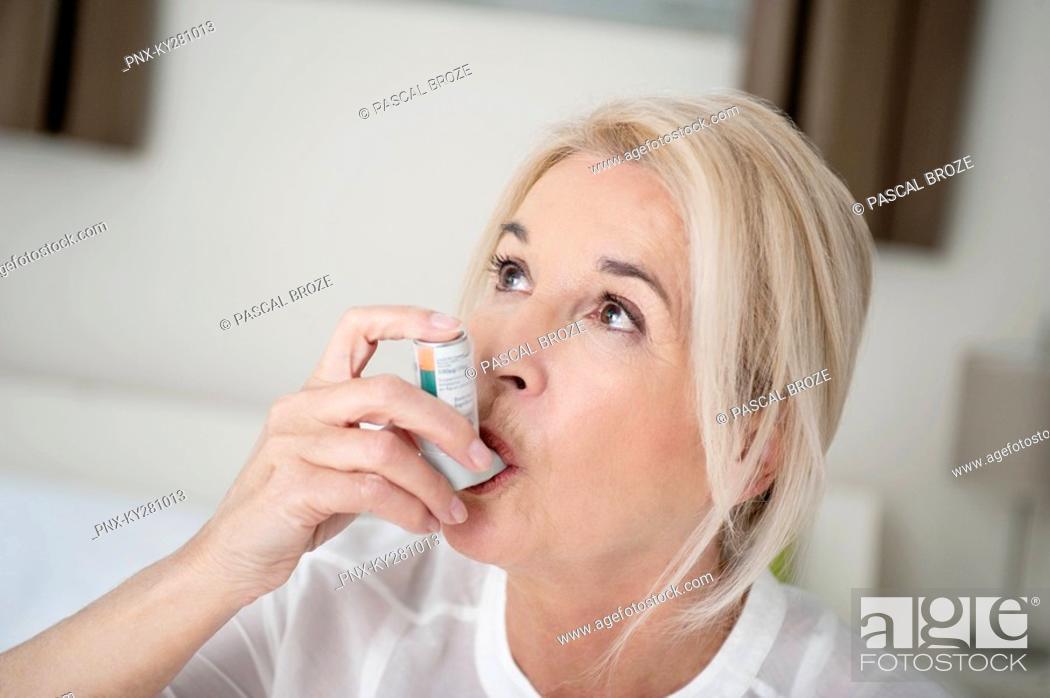 Stock Photo: Close-up of a woman using an asthma inhaler.