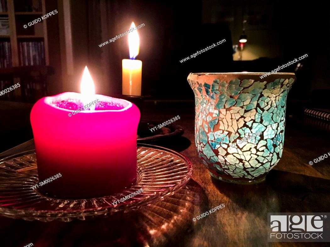 Imagen: Tilburg, Netherlands. Burning candles on a living room tabale during the darkest days of the year, just before Christmas.