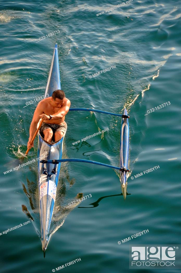 Stock Photo: Man paddles outrigger canoe.