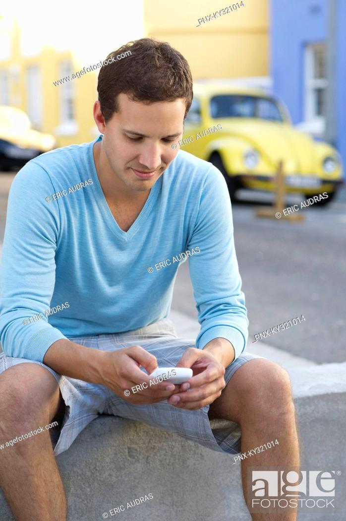 Stock Photo: Mid adult man text messaging with a mobile phone.