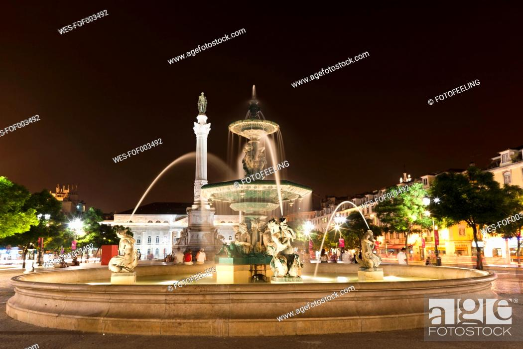 Stock Photo: Europe, Portugal, Lisbon, Baixa, View of Bronze fountain and statue of King Pedro IV in Rossio at night.