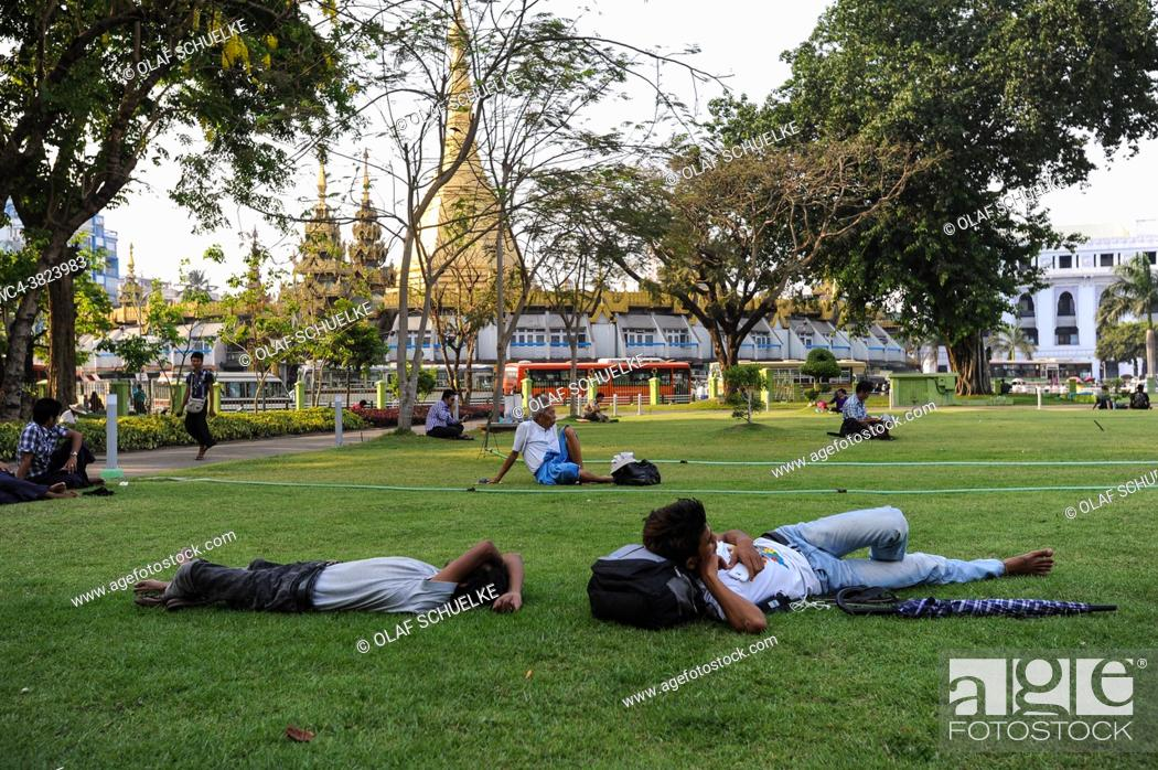 Stock Photo: Yangon, Myanmar, Asia - Locals relax on the lawn in the popular Maha Bandula Garden with the Sule Pagoda in the backdrop.