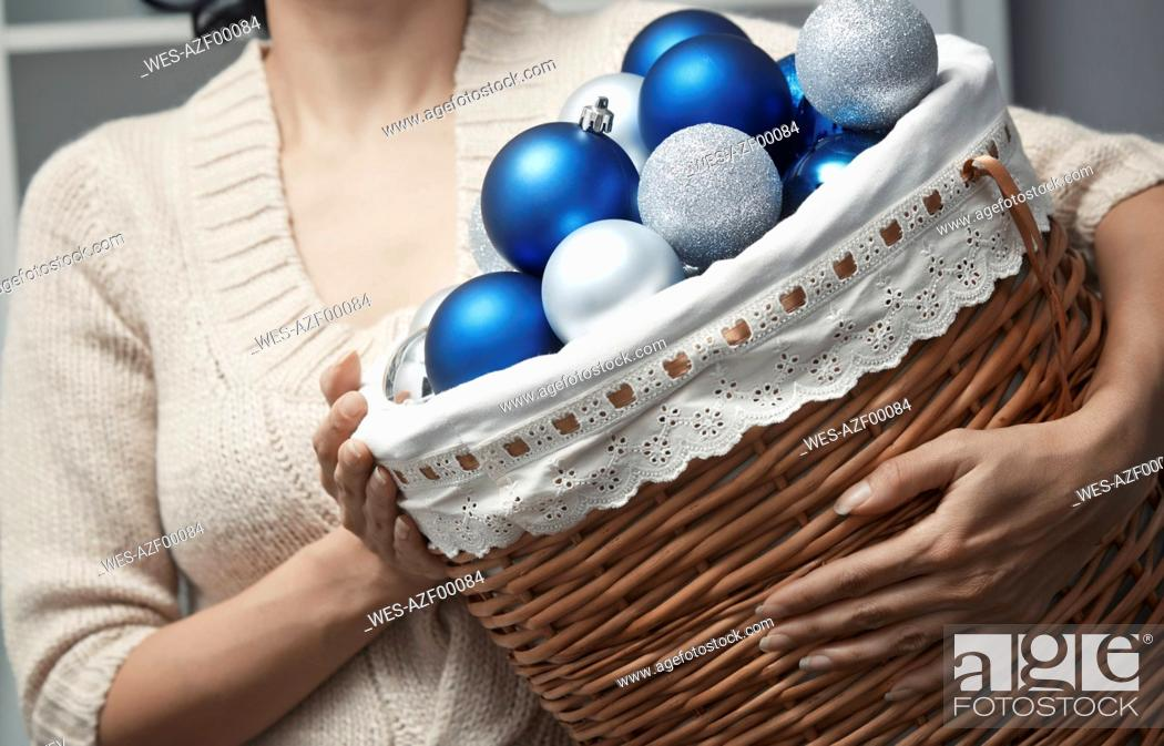 Stock Photo: Woman carrying basket full of Christmas baubles.