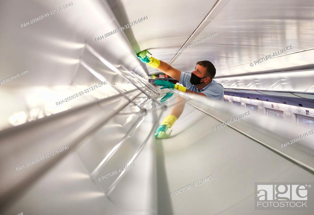 Stock Photo: 05 June 2020, North Rhine-Westphalia, Dortmund: An employee of DB-Fernverkehrswerk Dortmund cleans luggage racks in an ICE with face masks and rubber gloves.