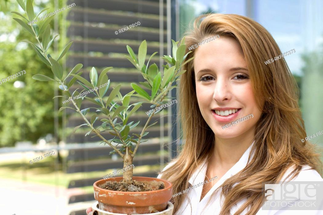 Stock Photo: Europe, Germany, North Rhine Westphalia, Duesseldorf, Young student with plant, smiling, portrait.