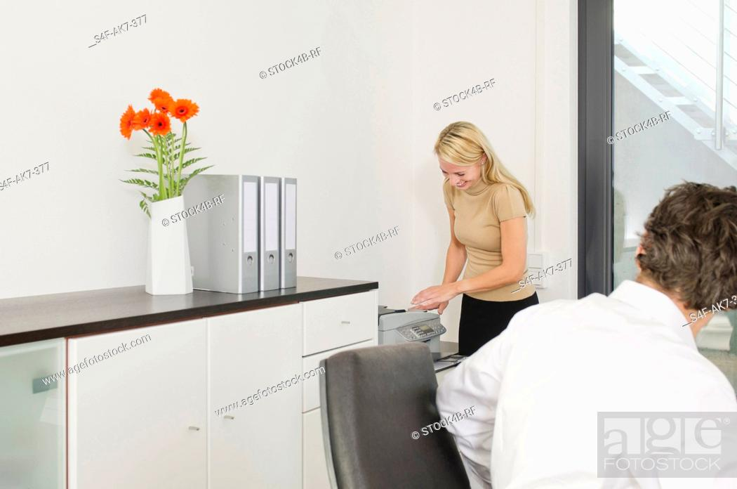 Stock Photo: Businessman looking at woman using photocopier.